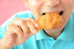 Young man eating deep fried chicken leg or drumstick Royalty Free Stock Image