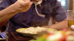 Young man eating delicious spaghetti carbonara with fork sprinkles parmesan cheese in cafe. 1920x1080. Young man eating delicious spaghetti carbonara with fork stock video footage