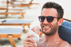 Young man eating doughnut on the beach Stock Photo