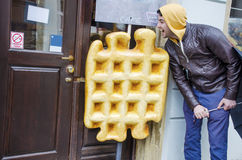 Young man eating enormous artificial waffle Stock Photo