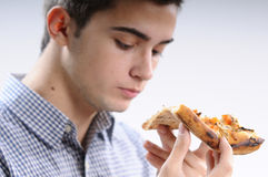 Young man eating food. White, young, handsome man  eating pizza Royalty Free Stock Photo