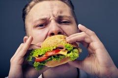 Young man eating a fresh burger. Beautiful Young man eating a fresh burger Royalty Free Stock Photo