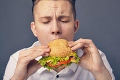 Young man eating a fresh burger. Beautiful Young man eating a fresh burger Stock Images