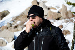 Young man eating fresh green apple in a winter mountain. Tourist  man eating fresh green apple in a winter mountain Stock Photography