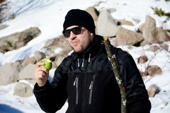 Young man eating fresh green apple in a winter mountain Stock Photos