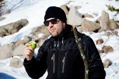 Young man eating fresh green apple in a winter mountain. Tourist  man eating fresh green apple in a winter mountain Stock Photos