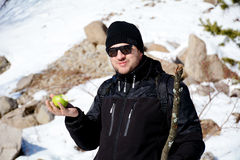 Young man eating fresh green apple in a winter mountain Stock Photo