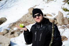 Young man eating fresh green apple in a winter mountain. Tourist  man eating fresh green apple in a winter mountain Royalty Free Stock Photos