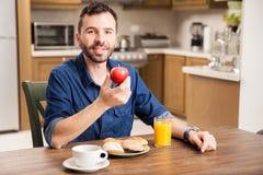 Young man eating fruit at home Stock Photos