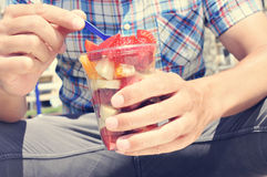 Young man eating a fruit salad outdoors Stock Photography