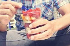 Young man eating a fruit salad outdoors Stock Photography