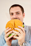 Young man eating a giant fake hamburger Stock Photos