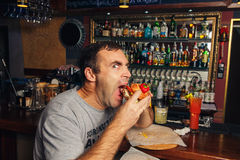 Young man eating a hamburger Stock Photos