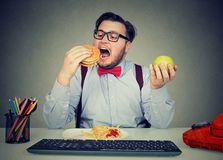 Obese employee eating fast food at workplace. Young man eating hamburger with fries instead of apple having sedentary way of life in office Royalty Free Stock Photography