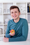 Young man eating an healthy apple in his kitchen Royalty Free Stock Photography