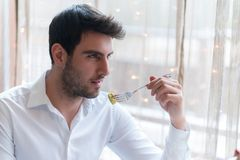 Young man eating a healthy food at restaurant. While talking with someone Royalty Free Stock Photography