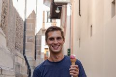 Young man eating ice cream in an alley stock photo