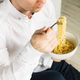 Young man is eating instant noodles from the white bowl. square. Young man is eating instant noodles from the white bowl stock photo