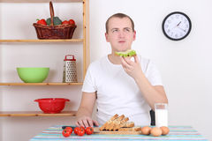 Young man eating in the kitchen Stock Image