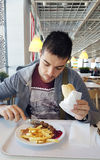 Young man eating meatballs garnished with french fries in a restaurant stock photography