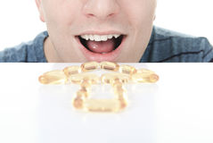 Young man is eating a omega-3 pill Stock Image