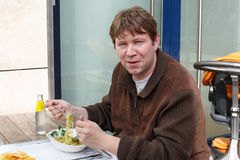 Young  man eating pasta in outdoor restaurant. Stock Photography