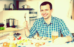 Young man eating pizza and salad in the kitchen at home Royalty Free Stock Photos