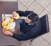 Young Man Eating Pizza. Upper view of a young man eating pizza in a restaurant Royalty Free Stock Images