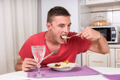 Young man eating a plate of spaghetti. And meat to satisfy his hunger, with a glass of white wine in the foreground Stock Photos