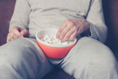 Young man eating popcorn Royalty Free Stock Photography
