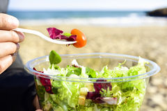 Young man eating a prepared salad outdoors stock photos