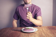 Young man eating purple pudding Royalty Free Stock Images