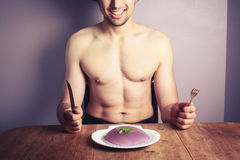 Young man eating purple pudding Royalty Free Stock Photography