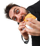 Young man while eating quickly a sandwich Royalty Free Stock Photos