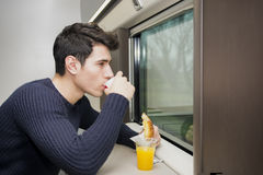 Young man eating refreshments on a train Stock Photo