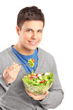 A young man eating salad. Isolated on white background stock image