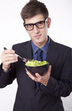 Young man eating salad. And smiling Royalty Free Stock Photography