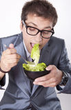 Young man eating salad. And smiling Royalty Free Stock Images