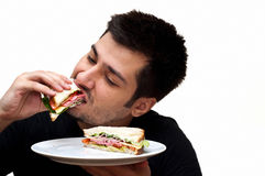 Young man eating a sandwich stock images
