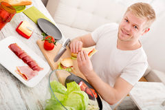 Young man eating a sandwich at home Stock Image