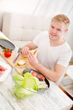 Young man eating a sandwich at home Royalty Free Stock Photography