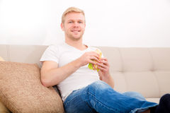 Young man eating a sandwich at home Royalty Free Stock Images
