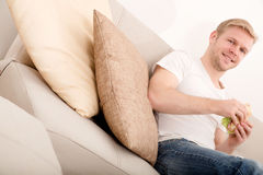 Young man eating a sandwich at home Royalty Free Stock Photo