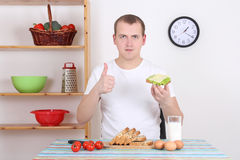 Young man eating sandwich in the kitchen Royalty Free Stock Image