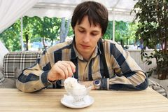 A young man is eating a scoop of ice cream from a vase in a summer cafe. Delicious kraft fruit ice cream.  Stock Images