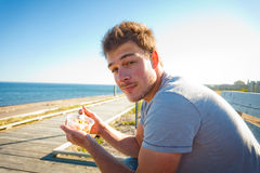 Young man eating on the beach Royalty Free Stock Image
