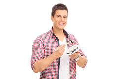 Young man eating sushi with Chinese sticks Stock Photos