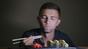 Young man eating sushi with chopsticks stock video