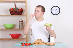 Young man eating tasty sandwich in the kitchen Stock Photo