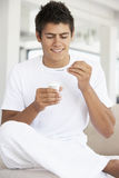 Young Man Eating Yogurt Royalty Free Stock Images